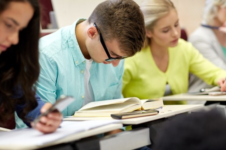 shortsighted: education, high school, university, learning and people concept - male student in glasses reading book at lecture Stock Photo