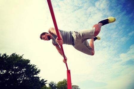 Fitness, Sport, Training und Lifestyle-Konzept - junger Mann auf horizontaler Balken im Freien ausüben Standard-Bild