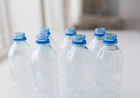 food storage: recycling, healthy eating and food storage concept - close up of open plastic bottles with pure drinking water on table Stock Photo