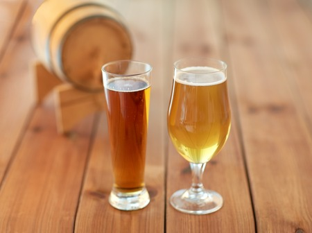 alehouse: brewery, drinks and alcohol concept - close up of different beers in glasses and barrel on wooden table