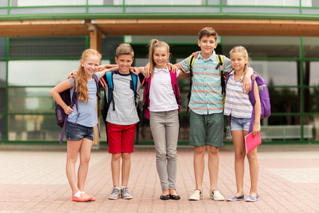 primary education, friendship, childhood and people concept - group of happy elementary school students with backpacks hugging outdoors