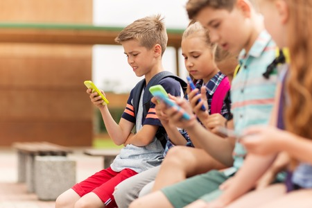 primary education, friendship, childhood, technology and people concept - group of happy elementary school students with smartphones and backpacks sitting on bench outdoors 스톡 콘텐츠