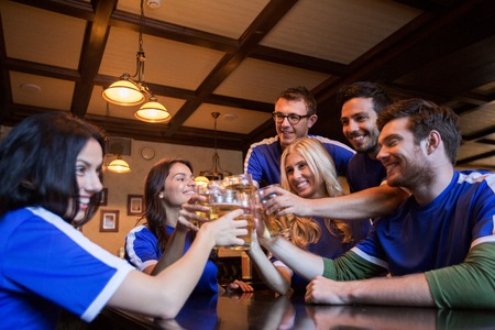 sports bar: sport, soccer, people and leisure concept - happy friends or football fans clinking beer glasses at bar or pub Stock Photo