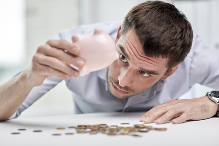 business, people, finances, crisis and money saving concept - businessman shaking piggy bank and getting coins at office Stock Photo