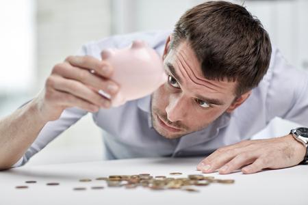 derrumbe: negocio, la gente, las finanzas, la crisis y el concepto de ahorro de dinero - hombre de negocios dando alcancía y conseguir las monedas en la oficina Foto de archivo