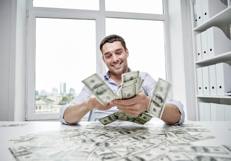 gente exitosa: business, people, success and fortune concept - happy businessman with heap of dollar money in office Foto de archivo