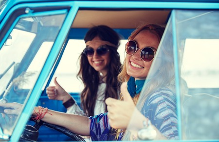 summer holidays, road trip, vacation, travel and people concept - smiling young hippie women driving and showing thumbs up gesture in minivan car