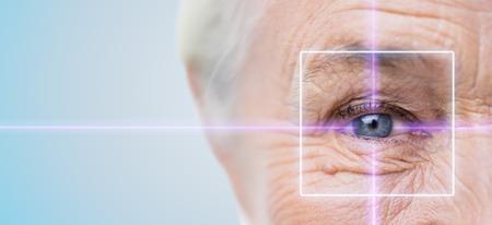 Leeftijd, visie, operatie, gezichtsvermogen en mensenconcept - close-up van senior vrouwelijk gezicht en oog met laserlicht Stockfoto
