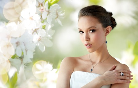 jewelry background: beauty, jewelry, people and luxury concept - beautiful asian woman or bride with earring, finger ring and pendant over natural spring cherry blossom background