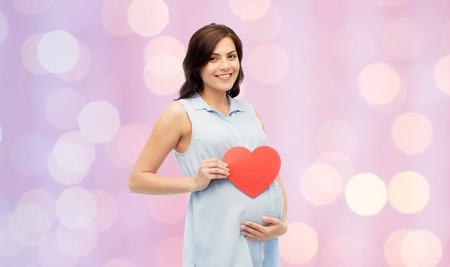 妊娠、愛、人と期待コンセプト - 赤いハート型のローズクォーツと安らぎの休日ライト背景に彼女の腹に触れるに幸せな妊娠中の女性