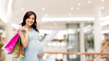 pregnancy, sale, motherhood, people and expectation concept - happy pregnant woman with shopping bags touching her big belly over mall background Stock Photo