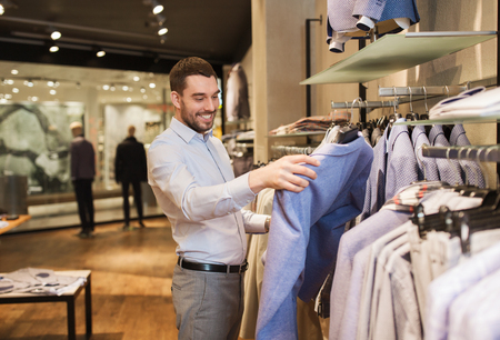 boutique: sale, shopping, fashion, style and people concept - happy young man in shirt choosing jacket in mall or clothing store Stock Photo