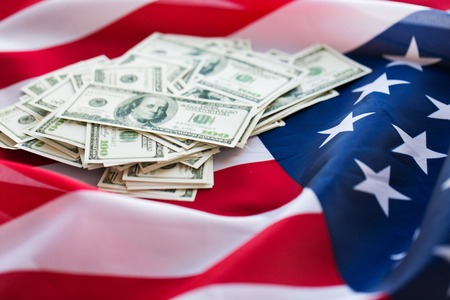nationalism: budget, finance and nationalism concept - close up of american flag and dollar cash money