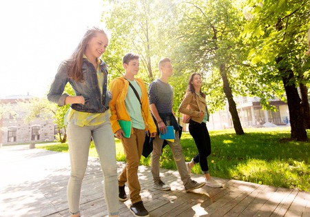 walking: education, high school, learning and people concept - group of happy teenage students walking outdoors