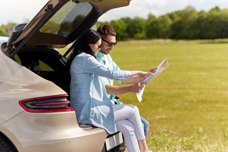 recreatie, weg reis, reizen en mensen concept - gelukkig man en vrouw op zoek locatie op de kaart zitten op de kofferbak van de auto hatchback openlucht Stockfoto