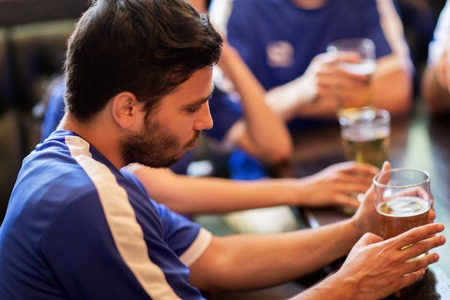 unhappy people: people, leisure, soccer and sport concept - unhappy football fans or friends with beer at bar or pub