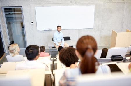estudiantes universitarios: la educación, la escuela secundaria, la universidad, la enseñanza y el concepto de la gente - grupo de estudiantes internacionales y el maestro con los papeles en la tarjeta blanca en conferencia