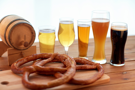 alehouse: brewery, drinks and food concept - close up of different beer glasses, wooden barrel and pretzels on table Stock Photo