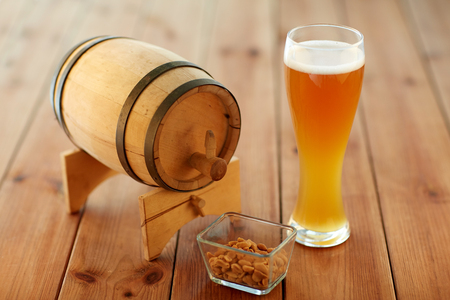 alehouse: brewery, drinks and alcohol concept - close up of draft lager beer in glass, peanuts and wooden barrel on table