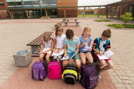 young boys: primary education, friendship, childhood, communication and people concept - group of happy elementary school students with backpacks and notebooks sitting on bench and doing homework outdoors