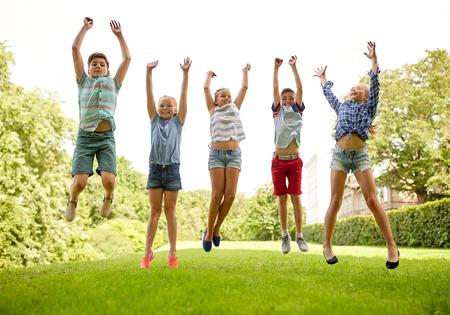 Vriendschap, jeugd, ontspanning en mensenconcept - groep gelukkige kinderen of vrienden springen en plezier in het zomervakantiepark