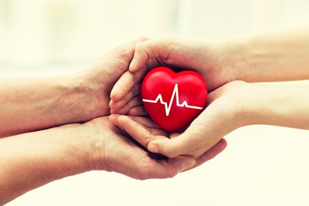 charity, health care, donation and medicine concept - man hand giving red heart with cardiogram to woman Standard-Bild