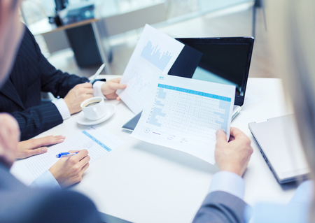 analyze: business and office concept - close up of business team with files and laptop computer in office