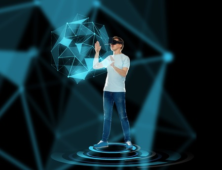 low glass: 3d technology, augmented reality, gaming, cyberspace and people concept - happy young man with virtual reality headset or 3d glasses playing game and touching low poly shape hologram