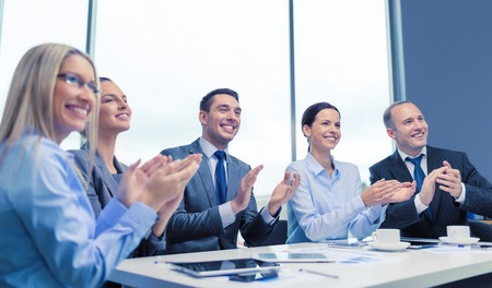 laptop computers: business, technology and office concept - happy business team with laptop computers, documents and coffee clapping hand