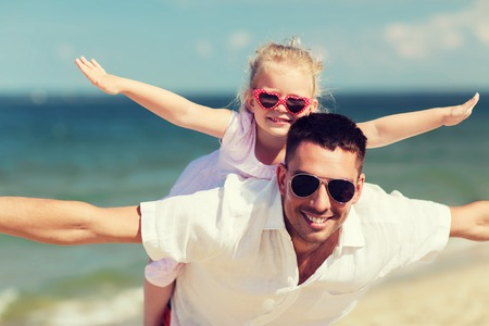 family, travel, vacation, adoption and people concept - happy father with little girl in sunglasses having fun on summer beach Stock Photo
