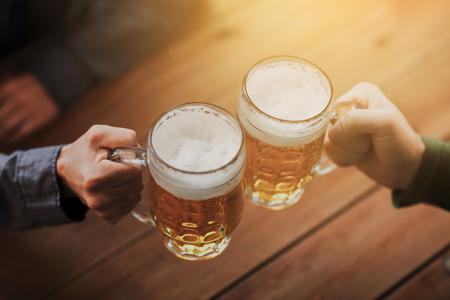 La gente, il tempo libero e bevande concept - stretta di mani maschili tintinnano boccali di birra al bar o pub Archivio Fotografico - 64305592