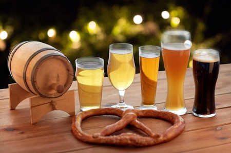brewery, drinks and food concept - close up of different beer glasses, wooden barrel and pretzel on table over holidays lights background Stok Fotoğraf - 64305613