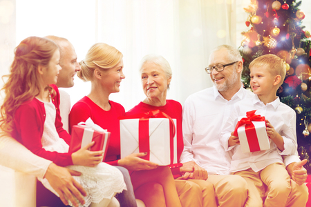 three generations of women: family, holidays, generation, christmas and people concept - smiling family with gift boxes sitting on couch at home