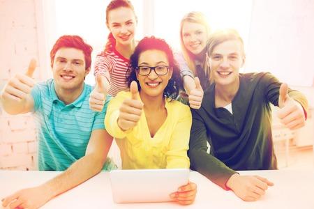 vzdělání, technologie a vysokoškolský koncept - pět studentů s úsměvem s počítačem tablet PC ve škole a ukazuje palce nahoru