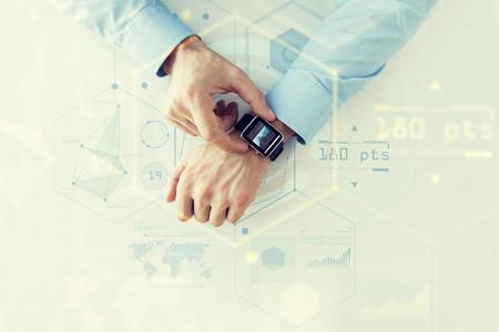 Unternehmen, zukünftige Technologie und Menschen Konzept - Nahaufnahme von männlichen Händen Smart Watch mit virtuellen Bildschirmen und Diagramme Projektion einstellen