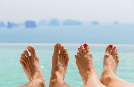 chiropody: summer holidays, beach, travel, leisure and body care concept - closeup of couple feet over sea and sky on beach
