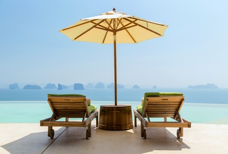 sunbeds: travel, vacation, tourism and luxury concept - beautiful view from infinity edge pool with parasol and sun beds for two at seaside