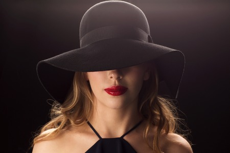 chic: people, luxury and fashion concept - beautiful woman in black hat over dark background Stock Photo