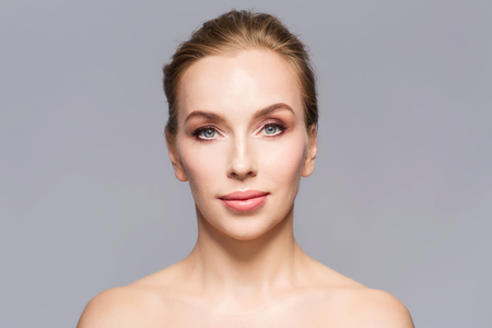 bare women: beauty, people and health concept - beautiful young woman face over gray background