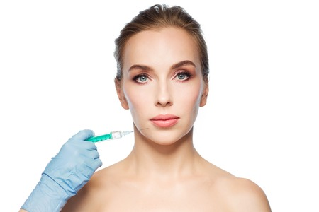 people, cosmetology, plastic surgery and beauty concept - beautiful young woman face and beautician hand in glove with syringe making injection over white background