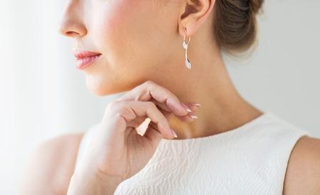 mujer elegante: glamour, belleza, joyas y el lujo concepto - cerca de la cara hermosa mujer con oro y pendientes de dia Foto de archivo