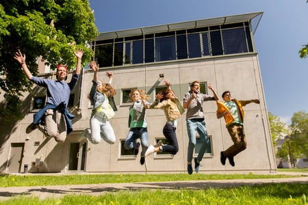 people in action: friendship, motion, action, freedom and people concept - group of happy teenage students or friends jumping outdoors