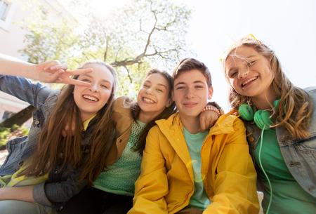 дружба и люди концепции - счастливые друзья-подростки или средней школы студенты с удовольствием и делая лица Фото со стока
