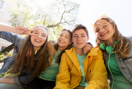 Konzept Freundschaft und die Menschen - glücklich Teenager Freunden oder High-School-Studenten, die Spaß haben und machen Gesichter Standard-Bild