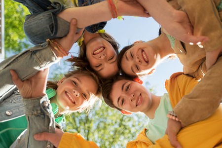 latin family: friendship and people concept - group of happy teenage friends holding hands outdoors Stock Photo