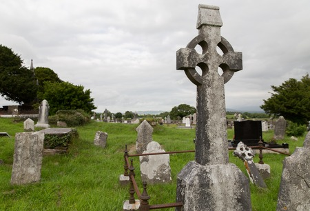 tombstones: ancient monument and burial concept - old headstones and ruins on celtic cemetery graveyard in ireland