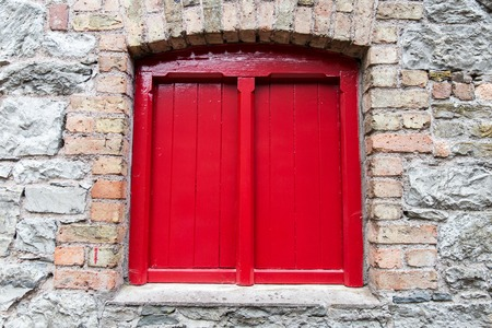 stone wall: architecture concept - close up of red vintage wooden window shutter in old stone wall