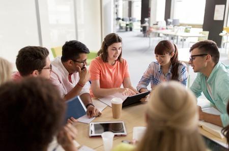 教育、高校、人と技術の概念 - 大学でタブレット pc コンピューター、書籍、ノート パソコンとテーブルに座って留学生のグループ