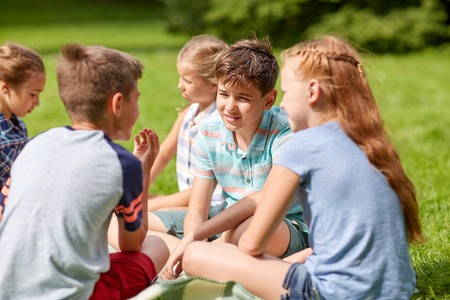 latin girls: friendship, childhood, leisure and people concept - group of happy kids or friends sitting on grass in summer park