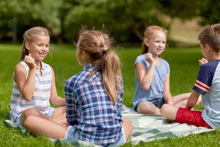 niños sentados: summer holidays, entertainment, childhood, leisure and people concept - group of happy pre-teen kids playing rock-paper-scissors game in park
